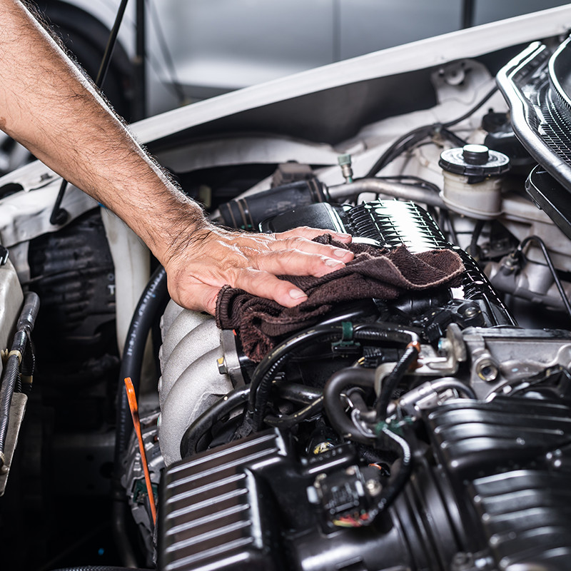 Close view of a man cleaning a car engine